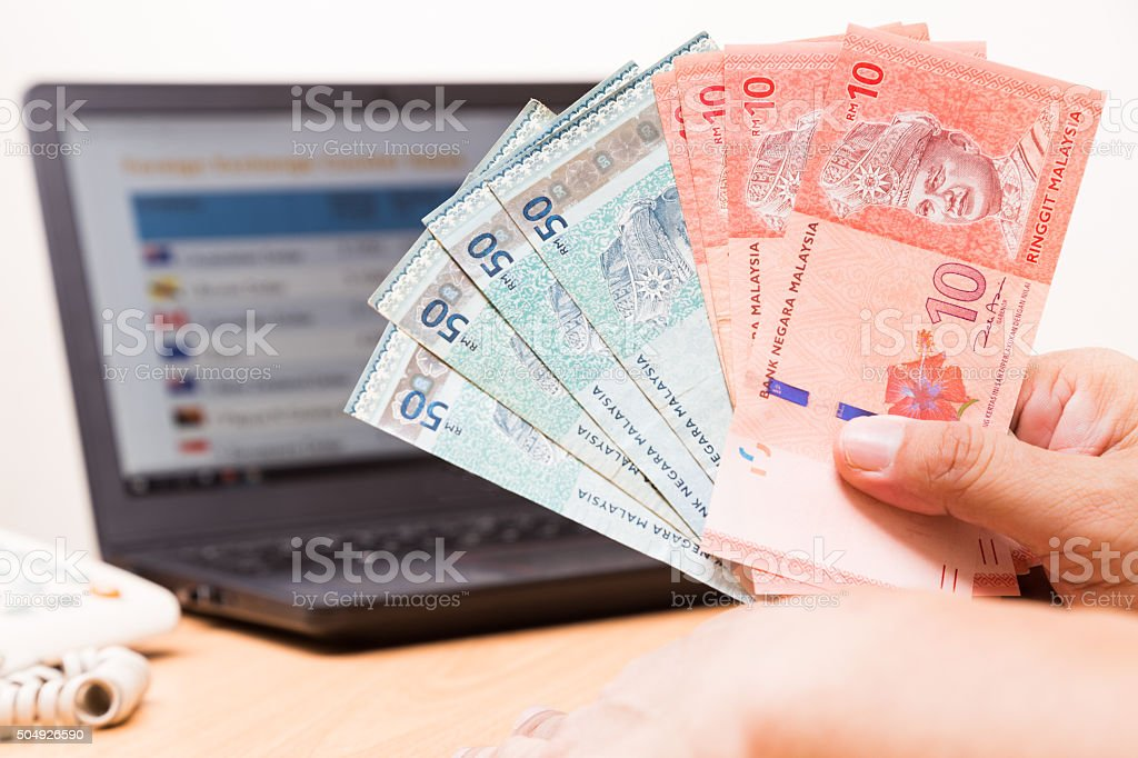 Hand holding Malaysia Ringgit in office with computer in backgro stock photo