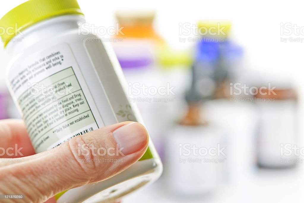 Hand holding medicine bottle stock photo