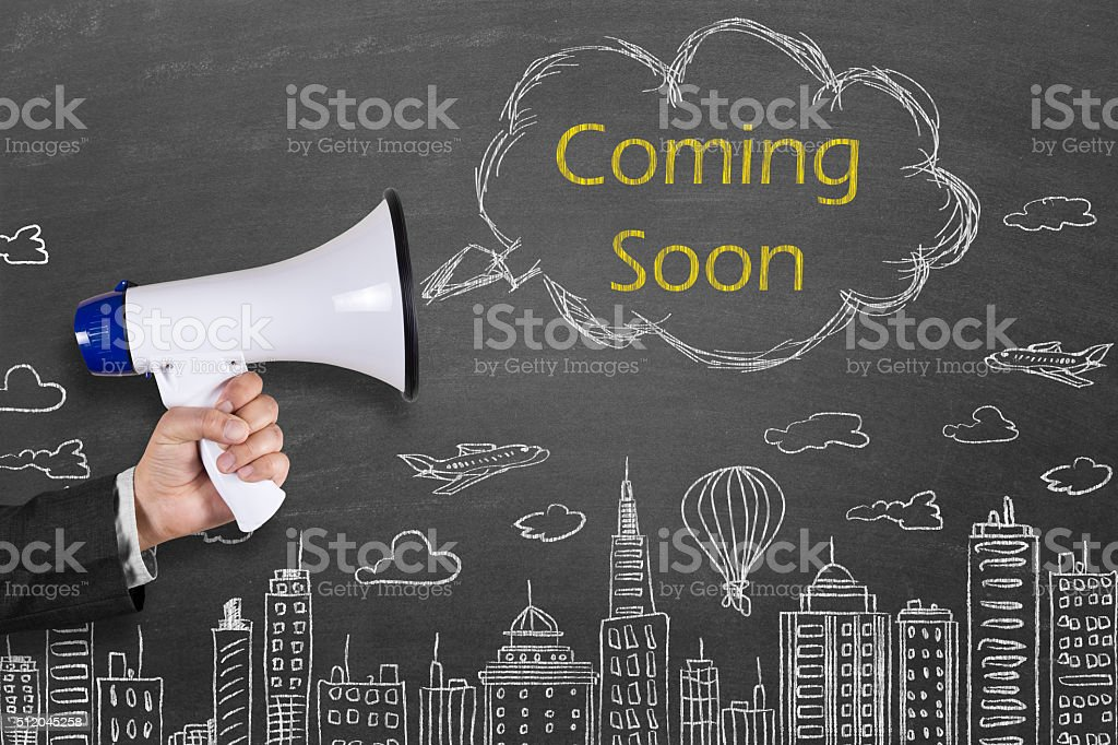 Hand holding megaphone with Coming Soon announcement stock photo