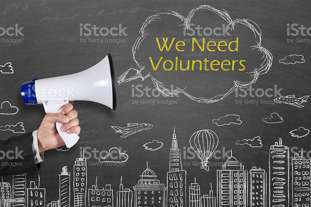 Hand holding megaphone with We Need Volunteers on cityscape background stock photo