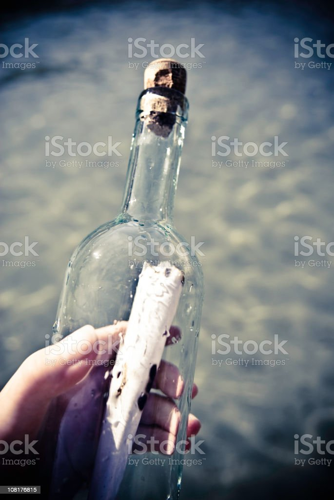 Hand Holding Message in a Bottle stock photo
