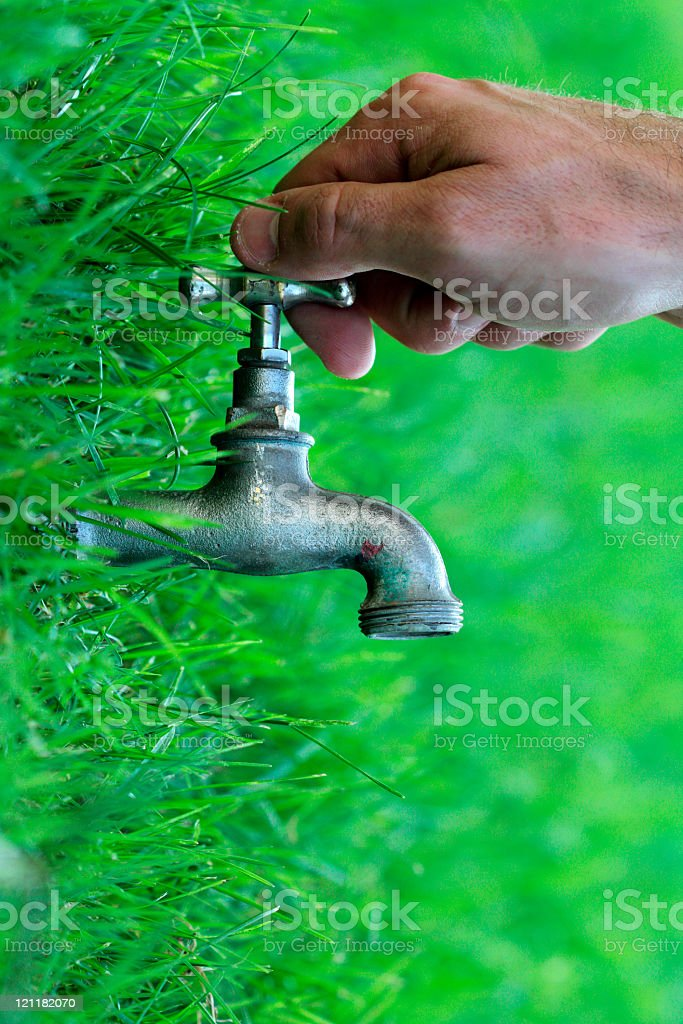Hand holding metal tap protruding from vibrant green grass royalty-free stock photo