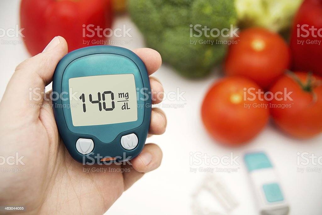 Hand holding meter. Diabetes doing glucose level test. stock photo