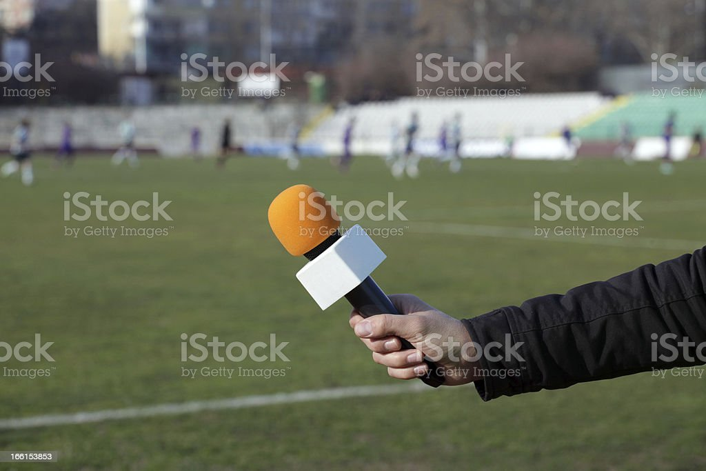 hand holding microphone for interview during a football mach royalty-free stock photo