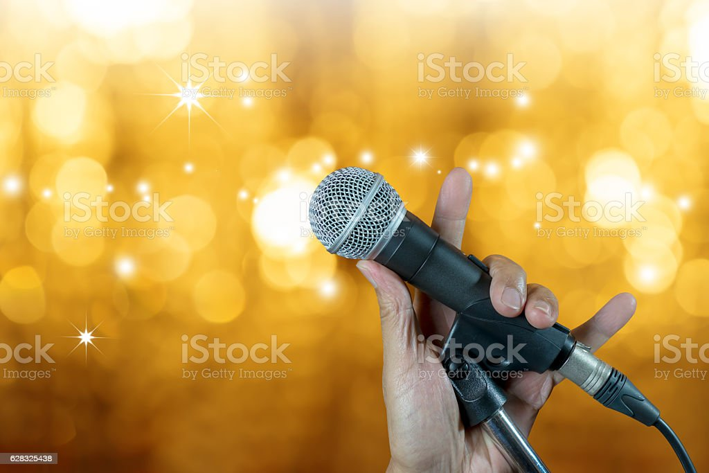 Hand holding microphone on stand with bokeh glow blurred background stock photo