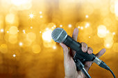 Hand holding microphone on stand with bokeh glow blurred background