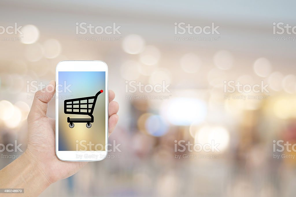 Hand holding mobile on shopping mall blur background , backgroun stock photo