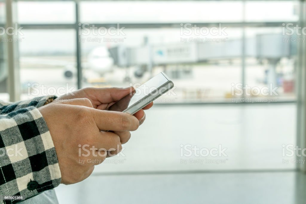 hand holding mobile phone in airport stock photo