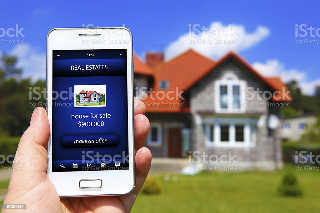 hand holding mobile phone with house sale offer stock photo