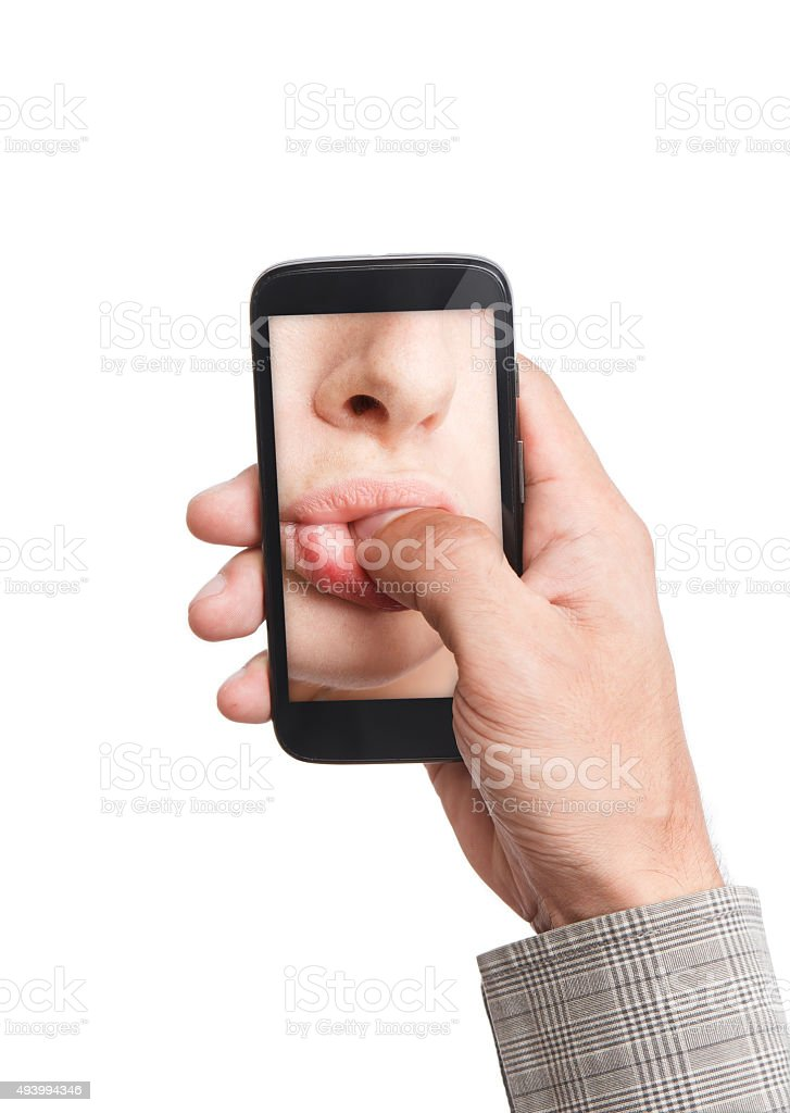 Hand holding mobile phone with lips sucking thumb stock photo