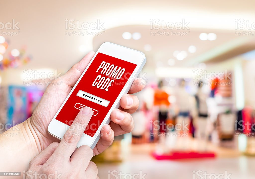 Hand holding mobile phone with promo code word stock photo