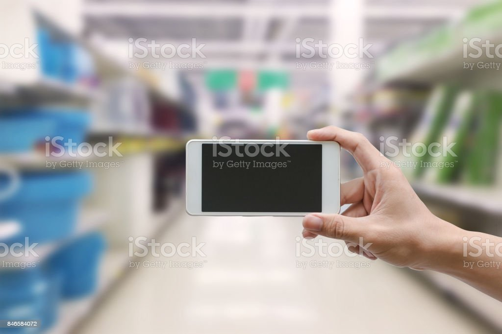 hand holding mobile smart phone with blank monitor screen on...