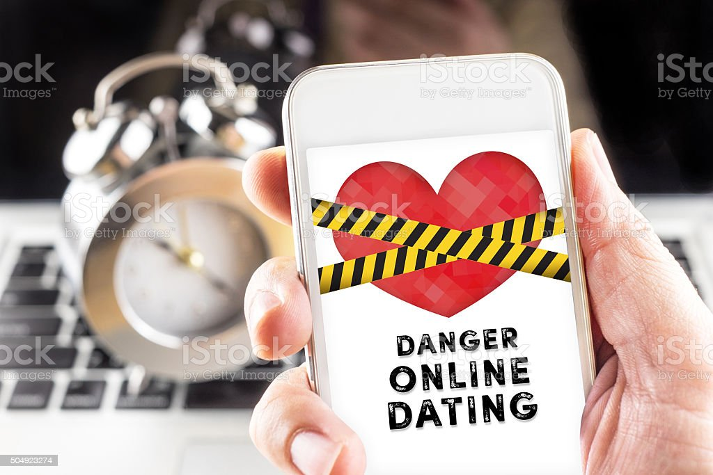 Hand holding mobile with caution tape on heart and Danger stock photo