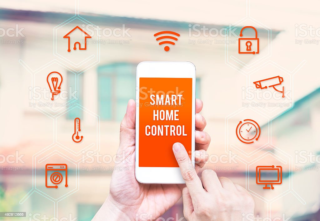 Hand holding mobile with home control application interface stock photo