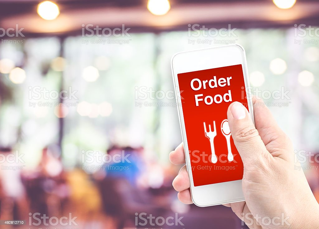 Hand holding mobile with Order food with blur restaurant stock photo