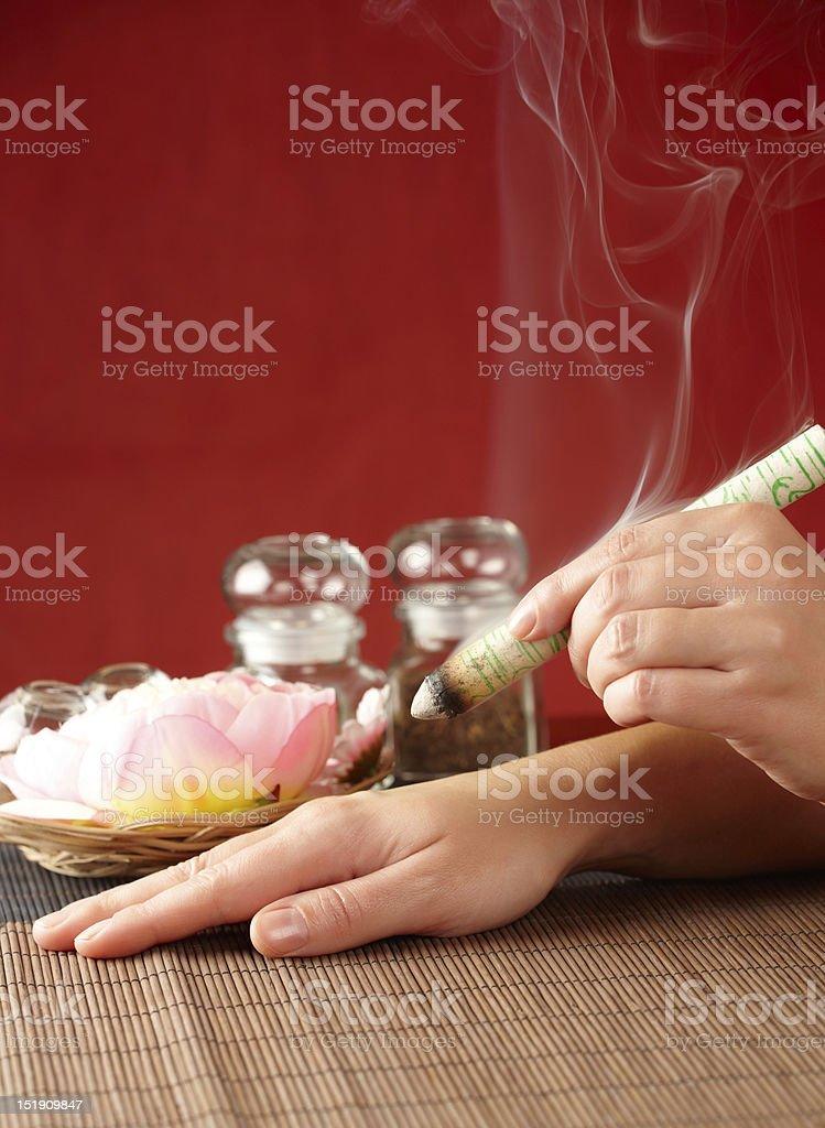 Hand holding moxa sticks on a bamboo mat stock photo