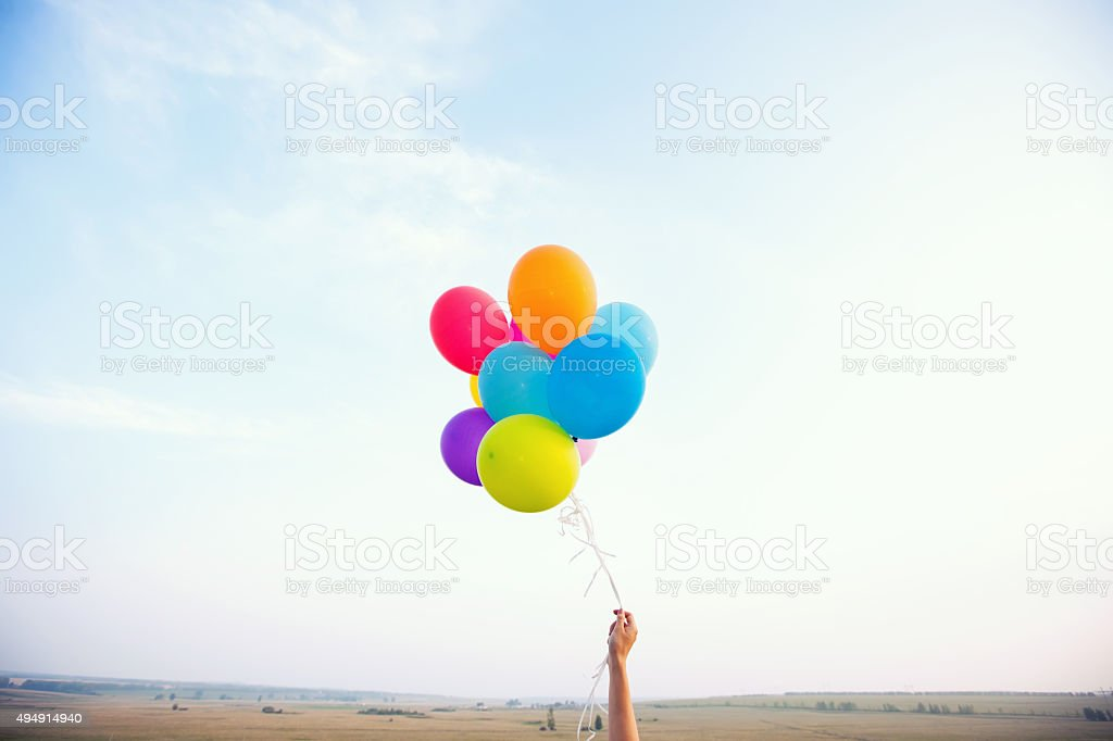 Hand holding multicolored balloons stock photo