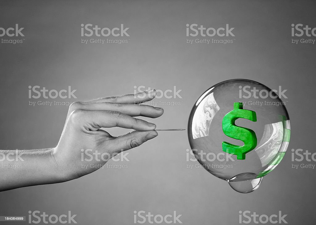 Hand holding needle about to pop bubble with dollar sign stock photo