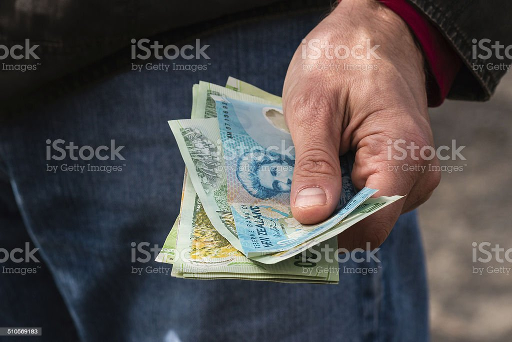 hand holding New Zealand dollars stock photo