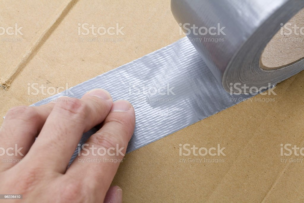 A hand holding on to silver duct tape stock photo