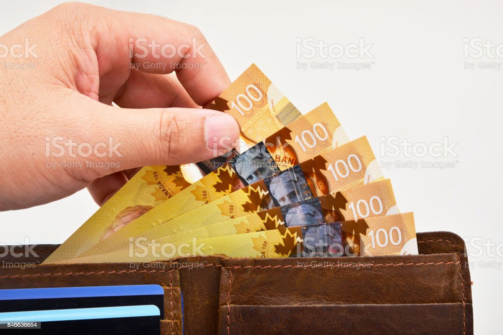 Hand holding one hundred Canadian banknotes (CAD) stock photo