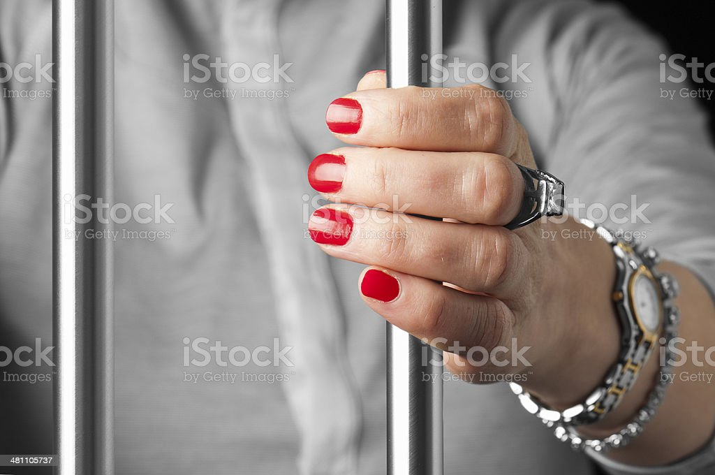 Hand holding onto prison bars from within cell stock photo