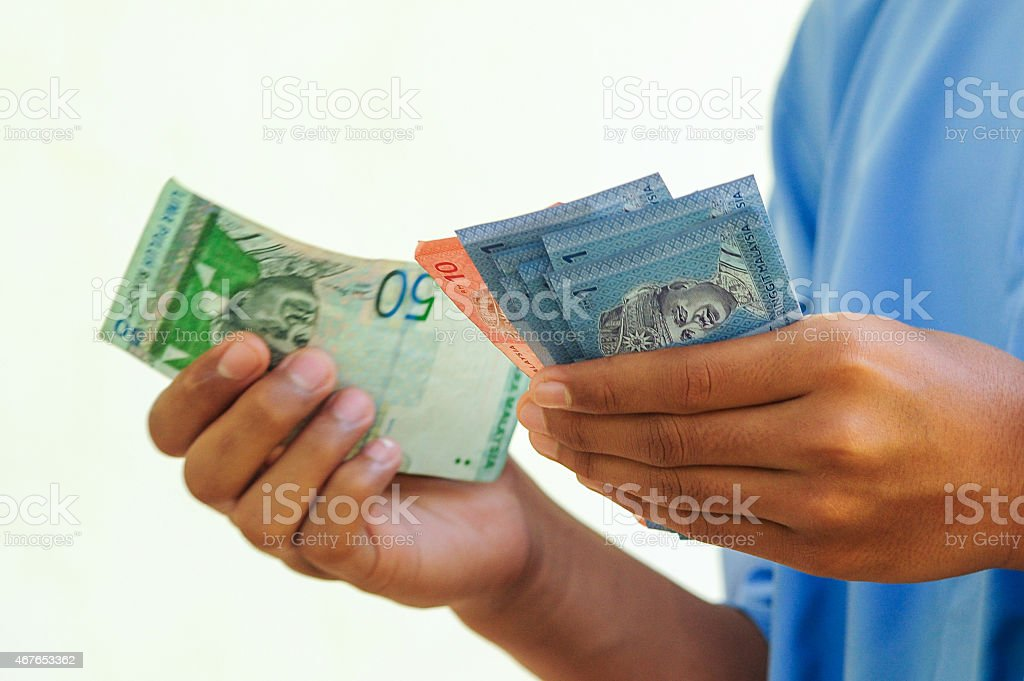 Hand holding or counting Malaysian Ringgit banknotes, selective stock photo