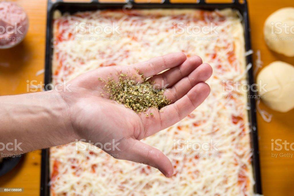 Hand holding oregano above pizza base stock photo