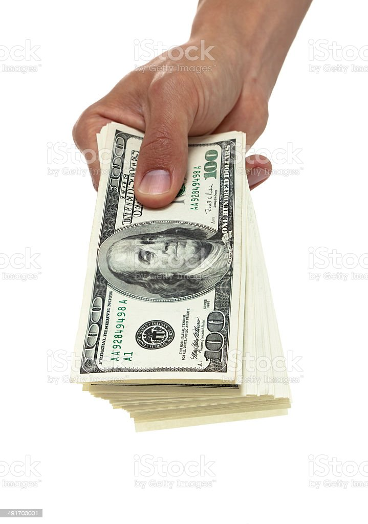 Hand holding out a stack of hundred dollar bills stock photo