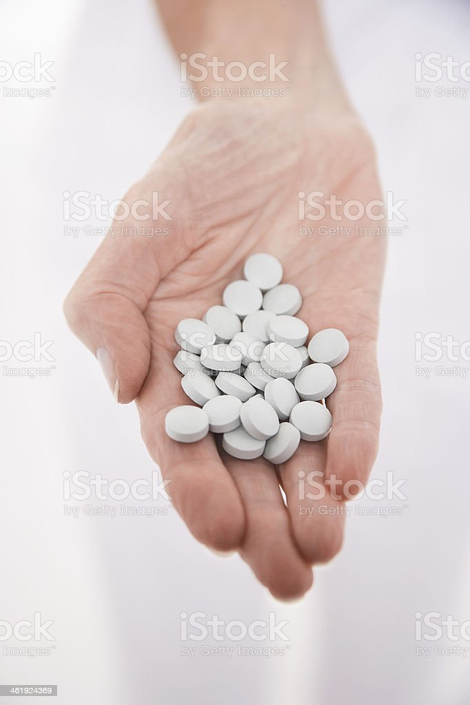 Hand Holding Out Many Pills stock photo