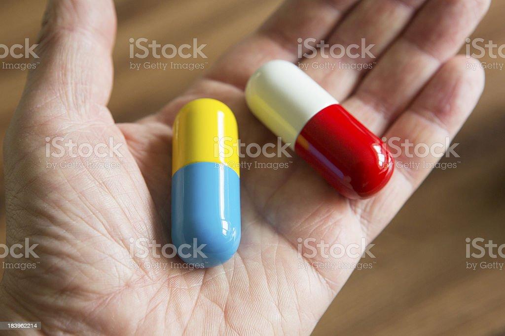 Hand Holding Oversized Medication Capsules royalty-free stock photo