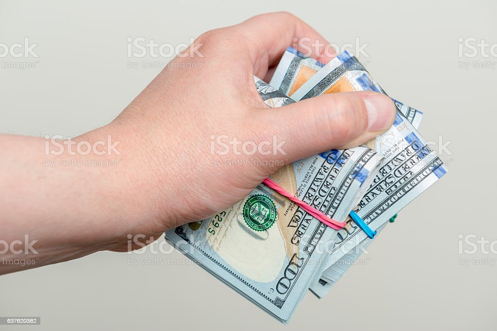 Hand holding packs of hundred dollar banknotes stock photo