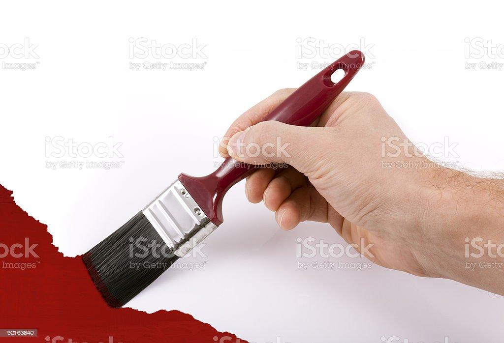 Рука держит Кисть картина стены с красной Стоковые фото Стоковая фотография