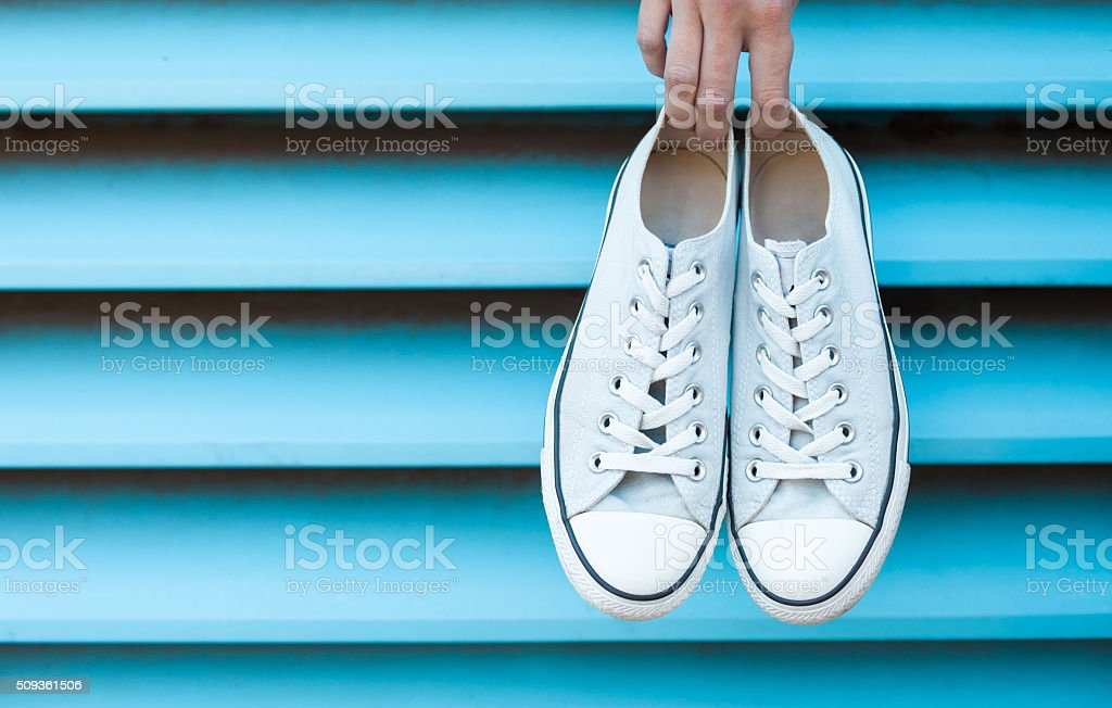 Hand holding pair of shoes stock photo