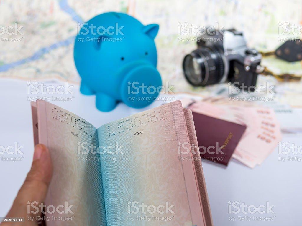 Hand holding passport book over piggy bank background/ saving concept stock photo