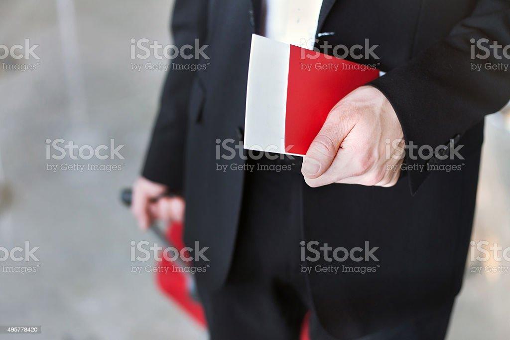 hand holding passport in airport stock photo