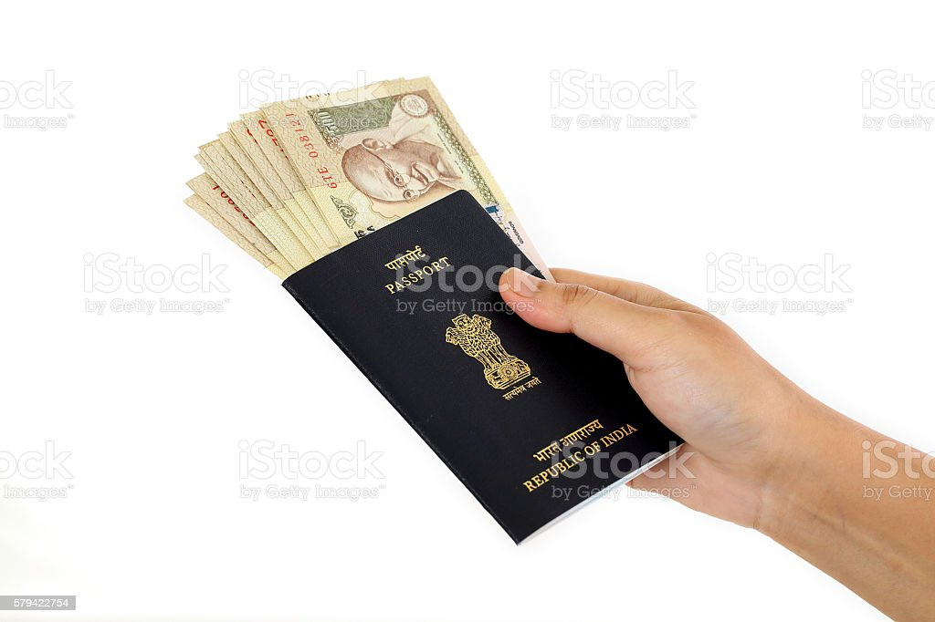 Hand holding passport with Indian currency stock photo