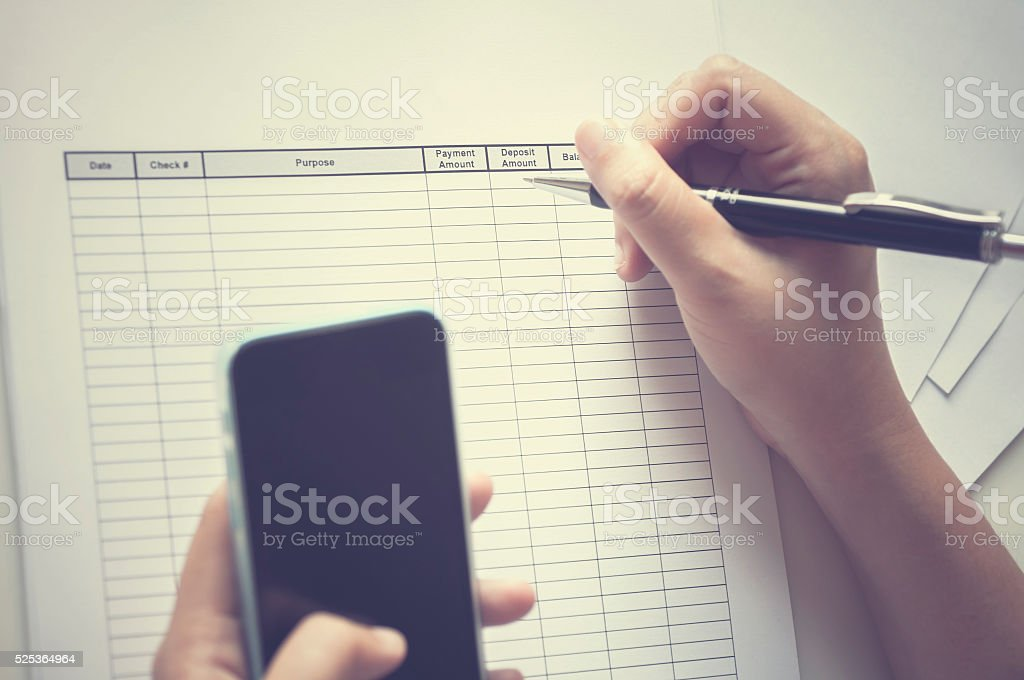 Hand holding pen over business form with mobile phone