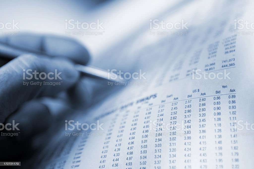 Hand Holding Pen Over Financial Newspaper royalty-free stock photo