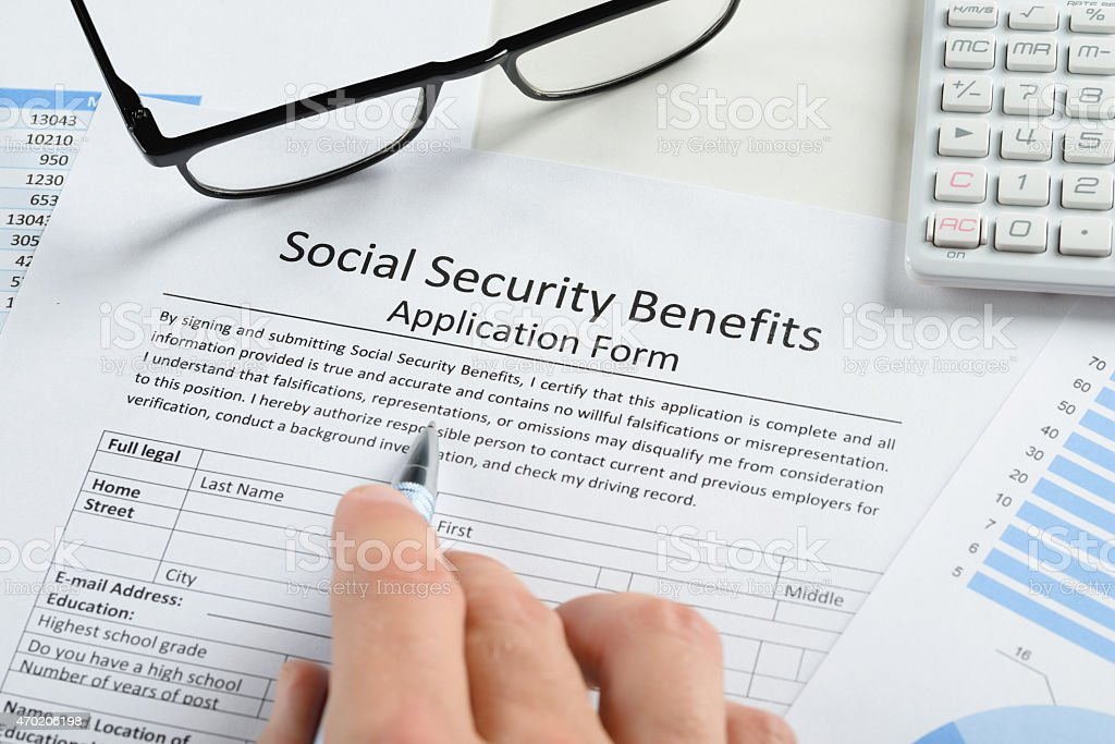 Hand Holding Pen Over Social Security Benefits Form stock photo