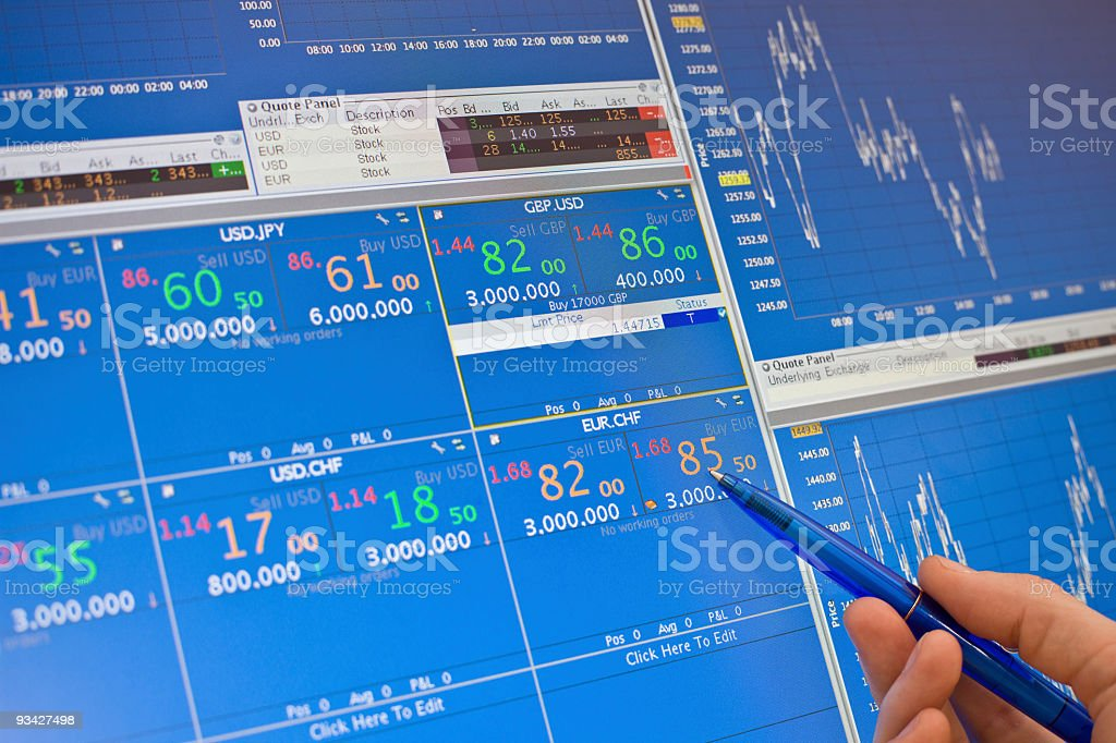 Hand holding pen points at trading charts royalty-free stock photo