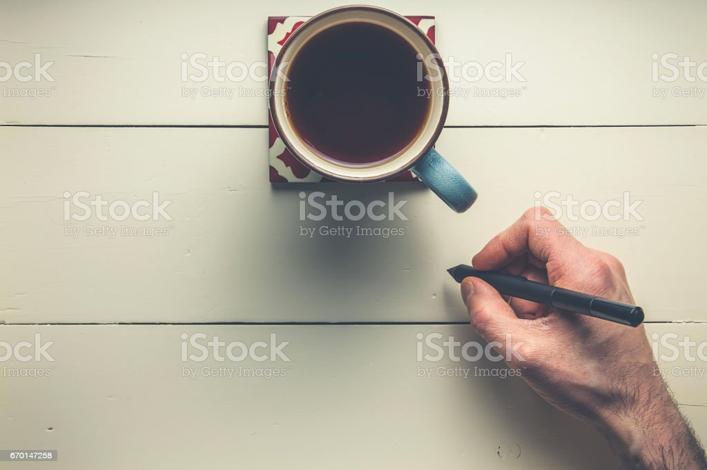 Hand holding pen with coffee on wood stock photo