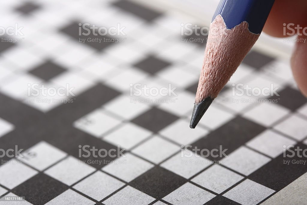 Hand holding pencil doing crossword puzzle stock photo