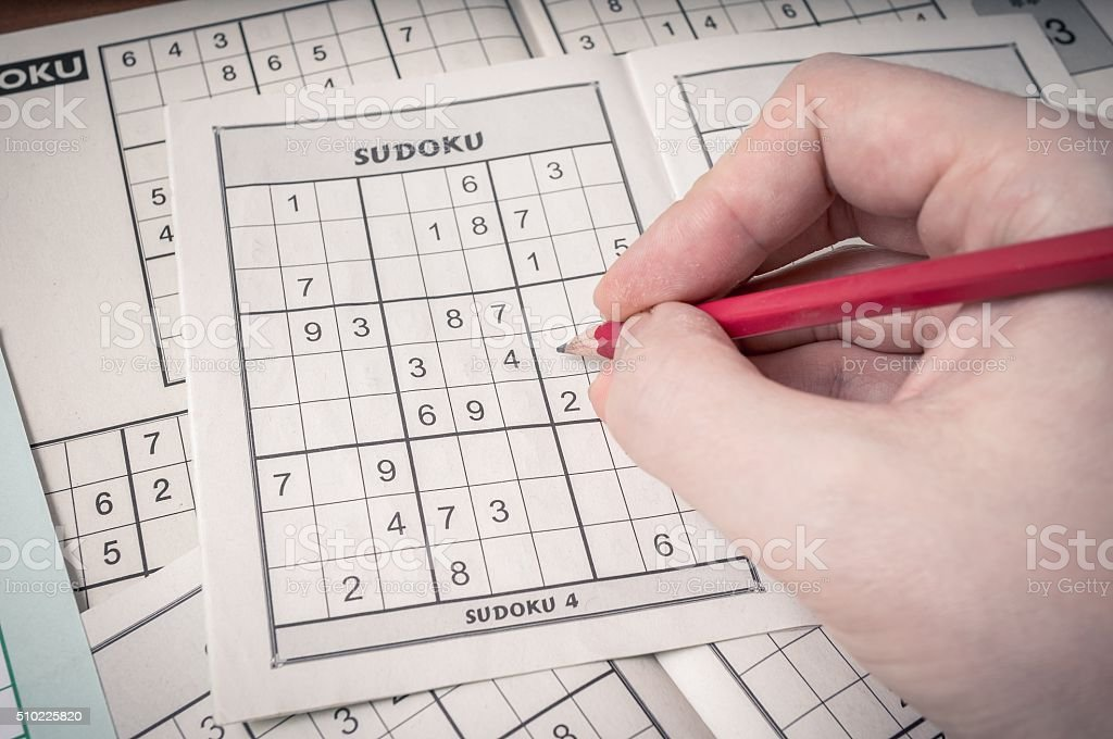Hand holding pencil is solving sudoku crossword. stock photo