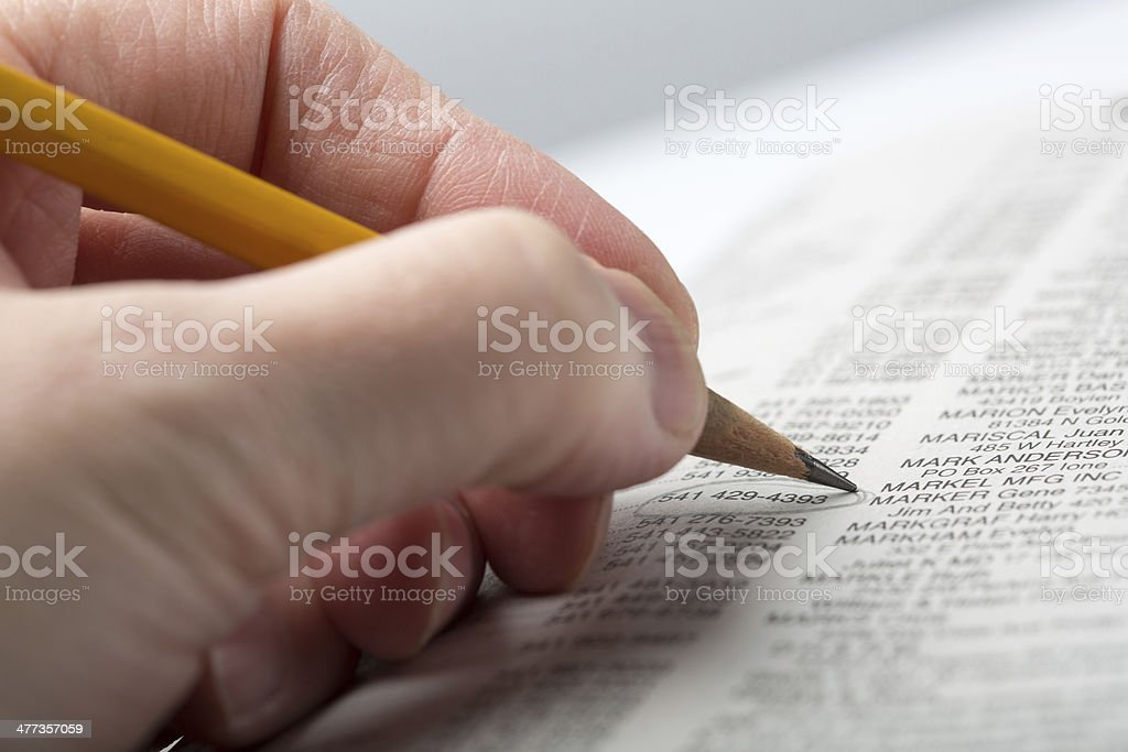 Hand holding pencil on phone book stock photo