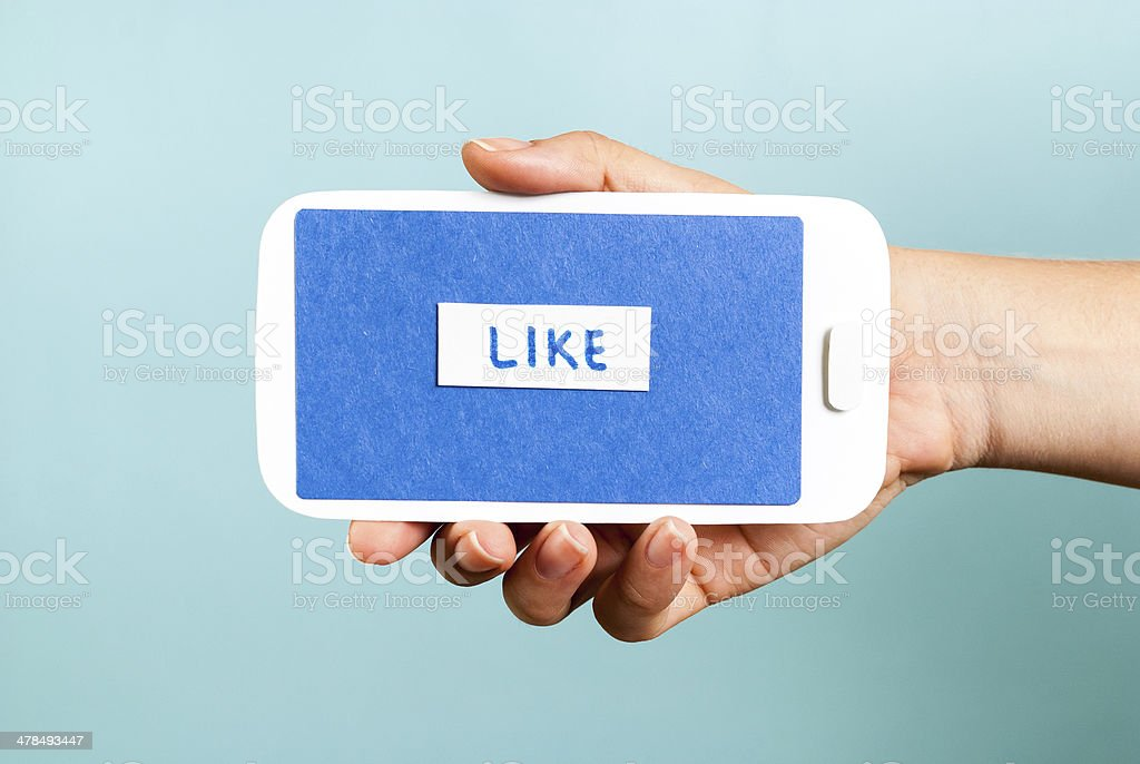Hand holding phone concept showing like button on blue background stock photo