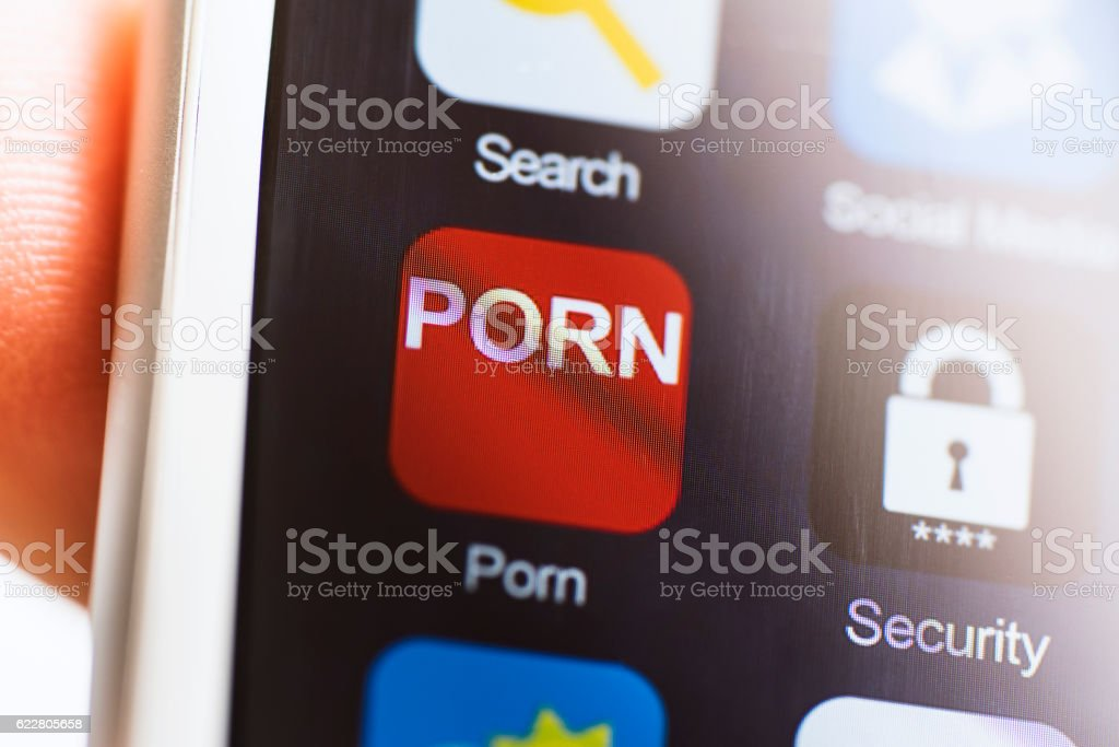 Hand holding phone, porn app icon on phone screen stock photo