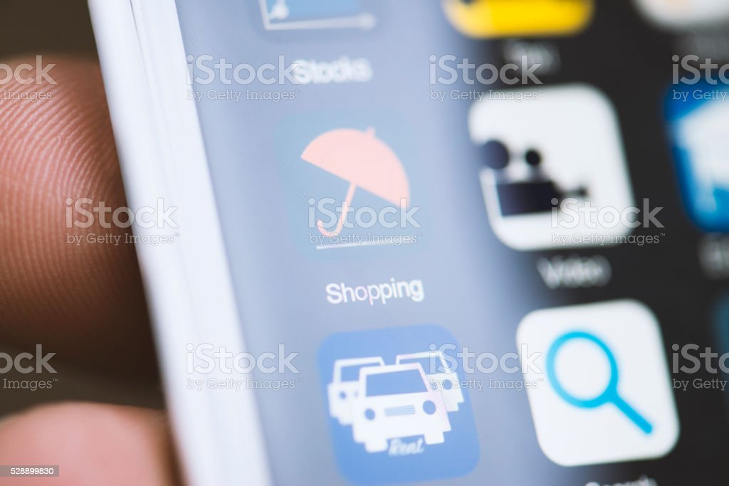Hand holding phone, shopping app on screen stock photo