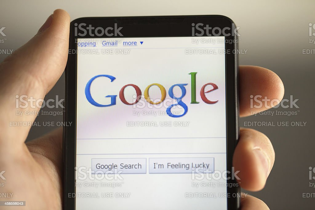 Hand holding phone showing Google search stock photo
