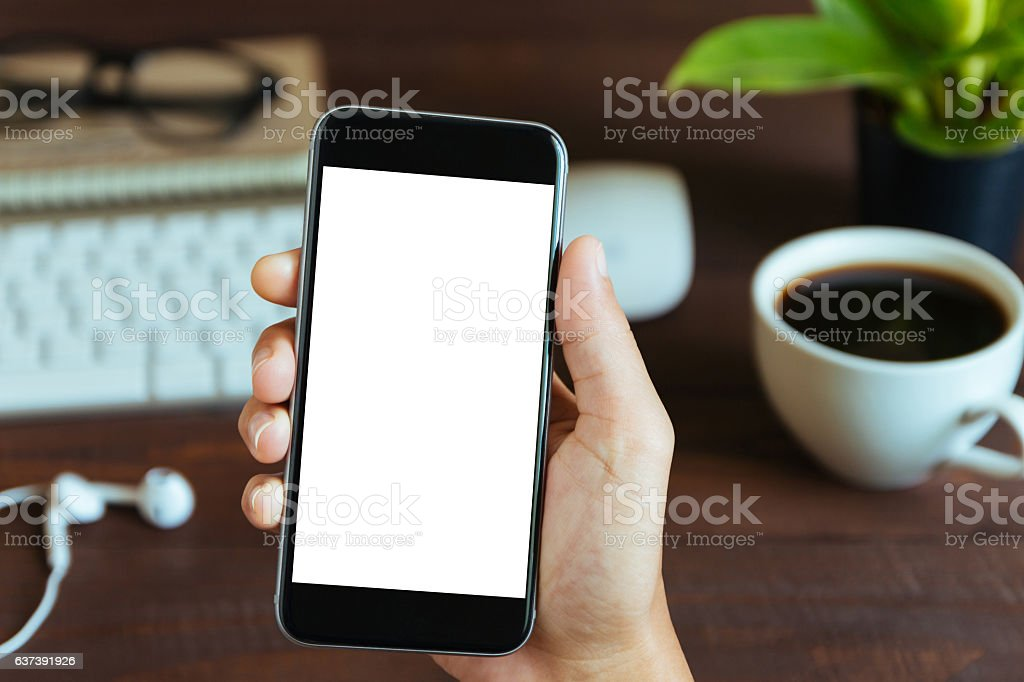 hand holding phone white screen over work table stock photo